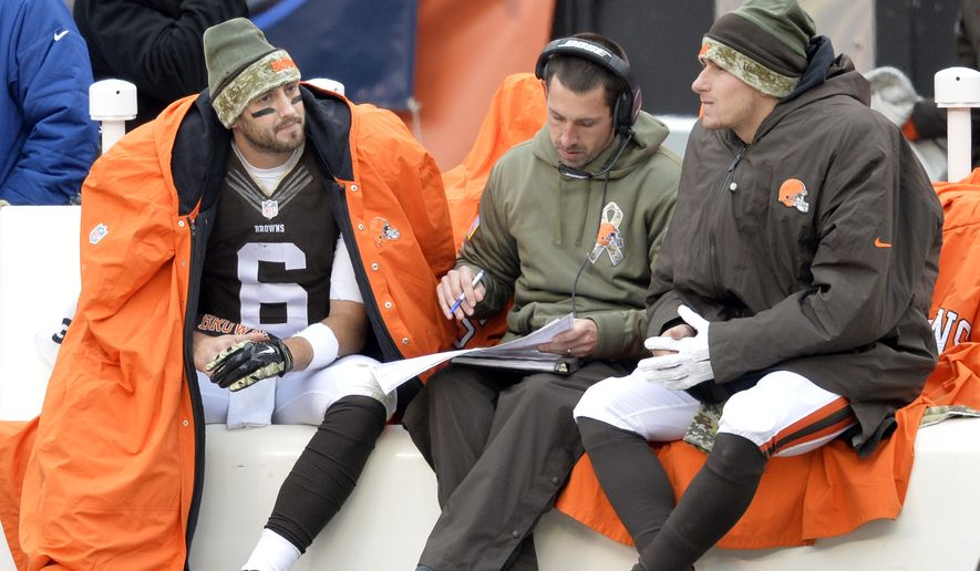 Cleveland Browns offensive coordinator Kyle Shanahan, center, goes over the play sheet with quarterbacks Brian Hoyer (6) and Johnny Manziel in the third quarter of an NFL football game against the Houston Texans Sunday, Nov. 16, 2014, in Cleveland. (AP Photo/David Richard)
