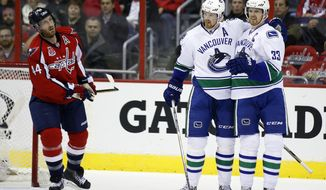 Vancouver Canucks left wing Daniel Sedin (22), from Sweden, and Vancouver Canucks center Henrik Sedin (33), from Sweden, celebrate Sedin's goal, with Washington Capitals defenseman Brooks Orpik (44) nearby, in the second period of an NHL hockey game, Tuesday, Dec. 2, 2014, in Washington. (AP Photo/Alex Brandon)