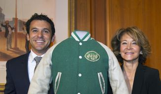 """Actor Fred Savage from the award-winning TV series: """"The Wonder Years,"""" left, his mother Joanne Savage, right, and his children Lilly, bottom left, and Oliver, bottom right, pose with his character's letterman jacket after they donated show memorabilia to the Smithsonian's National Museum of American History in Washington, Tuesday, Dec. 2, 2014. The Wonder Years aired  from 1988-1993 and depicted the everyday life of a boy growing up in an American suburb during the late 1960's and early 1970's. (AP Photo/Cliff Owen)"""