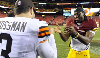 Cleveland Browns quarterback Rex Grossman (3) talks with Washington Redskins quarterback Robert Griffin III (10) after an NFL preseason football game Monday, Aug. 18, 2014, in Landover, Md. (AP Photo/Richard Lipski)