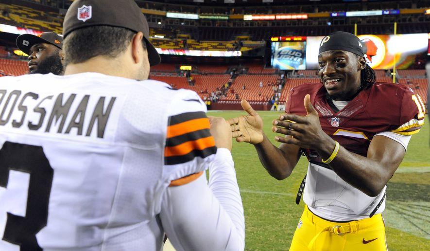 Cleveland Browns quarterback Rex Grossman (3) talks with Washington Redskins quarterback Robert Griffin III (10) after an NFL preseason football game Monday, Aug. 18, 2014, in Landover, Md. (AP Photo/Richard Lipski)