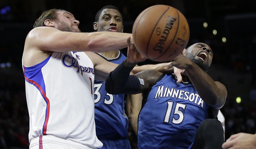 Minnesota Timberwolves' Shabazz Muhammad, right, is fouled by Los Angeles Clippers' Spencer Hawes as Timberwolves' Thaddeus Young, center, watches during the first half of an NBA basketball game Monday, Dec. 1, 2014, in Los Angeles. (AP Photo/Jae C. Hong)