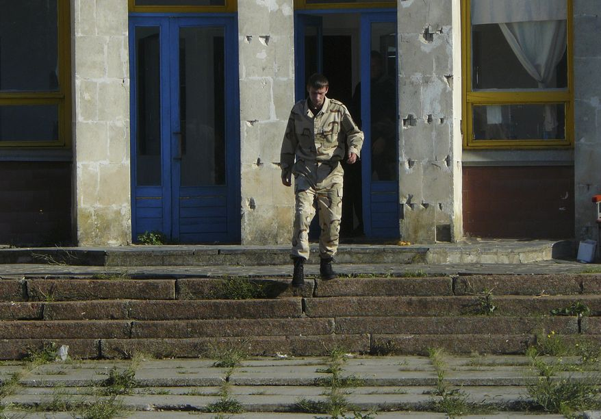 A man in camouflage guards and chases away any would-be visitors at the Dobrobut farm in Grabovo, Crimea in this photo taken on Tuesday, Oct.  28, 2014. Dobrobut was one of dozens of businesses to be forcibly taken over this year by Crimea's new pro-Moscow leaders. (AP Photo/Laura Mills)