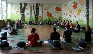 In this Oct. 1, 2014 file photo, students meditate during Mindful Studies class at Wilson High School in Portland, Ore. College students on some campuses are investigating meditation as well. (AP Photo/Gosia Wozniacka)
