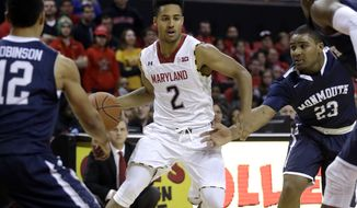 Maryland guard Melo Trimble (2) drives past Monmouth defenders during an NCAA college basketball game, Friday, Nov. 28, 2014, in College Park, Md. (AP Photo/Patrick Semansky)