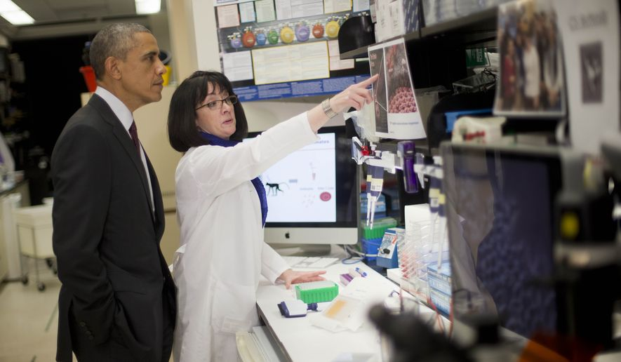 President Barack Obama listens as Dr. Nancy Sullivan, Senior Investigator; Chief, Biodefense Research Section, National Institute of Allergy and Infectious Diseases, during a NIH tour of the Vaccine Research Center at the National Institutes of Health (NIH), Tuesday, Dec. 2, 2014, in Bethesda, Md. (AP Photo/Pablo Martinez Monsivais)