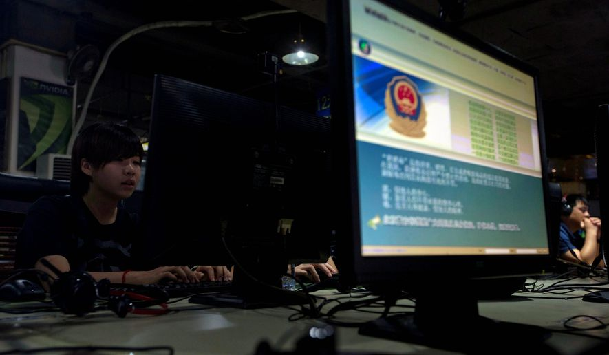 Computer users sit near a display with a message from the Chinese police on the proper use of the Internet at an Internet cafe in Beijing, China, in this Aug. 19, 2013, file photo. (AP Photo/Ng Han Guan, File)