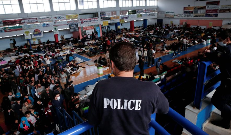 A policeman observes the scene as immigrants who arrived aboard a cargo ship from Turkey line up for meals while others sit on bedding in a basketball arena, where they have been given temporary shelter. Many refugees, often soaked from the sea crossing, spend days sleeping outdoors or squashed into tiny cells before being moved. (Associated Press)