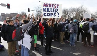 East High School students participate in a protest against the Ferguson, Missouri grand jury decision, at a busy intersection in front of the state Capitol in Denver, Wednesday Dec. 3, 2014. Authorities said four Denver police officers were hit by a car while watching the high school students protest.  (AP Photo/Brennan Linsley)
