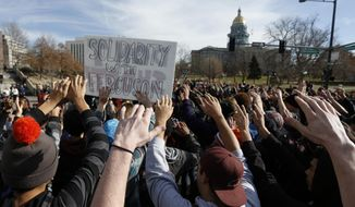 East High School students participate in a protest against the Ferguson, Missouri grand jury decision, in a busy intersection in front of the state Capitol in Denver, Wednesday Dec. 3, 2014. A grand jury's decision last week not to charge Officer Darren Wilson in the shooting death of Michael Brown has sparked demonstrations across the country. (AP Photo/Brennan Linsley)