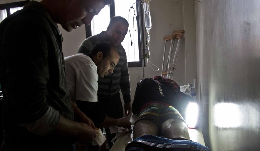 In this Nov. 21, 2014 photo, Dr. Mohammed Arif helps to deal with a wounded patient at a field hospital in Kobani, Syria. Like much of this besieged Syrian border town, most of its medical clinics are now in ruins. Only one still stands _ its location a secret for fear it will be targeted. A small team of three doctors and five nurses work at this aid station, treating the flood of Kurdish and Free Syrian Army fighters who are holding the Islamic State militants at bay. (AP Photo/Jake Simkin)