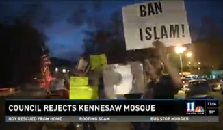 """A group of anti-Muslim protesters carrying signs that read """"Ban Islam"""" and """"Islam Wants No Peace!"""" gathered outside of Kennesaw City Hall as the council voted 4-1 against a Muslim group's request to rent a retail space in the city to be used as a mosque. (11 Alive News)"""