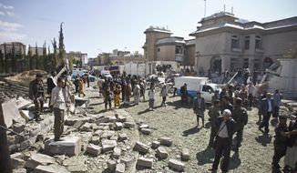 Security forces and civilians gather at the damaged residence of the Iranian ambassador after a car bomb attack in Sanaa, Yemen, Wednesday, Dec. 3, 2014. A massive car bomb exploded Wednesday morning in the Yemeni capital, Sanaa, apparently targeting the home of the Iranian ambassador, Yemeni security officials said. (AP Photo/Hani Mohammed)