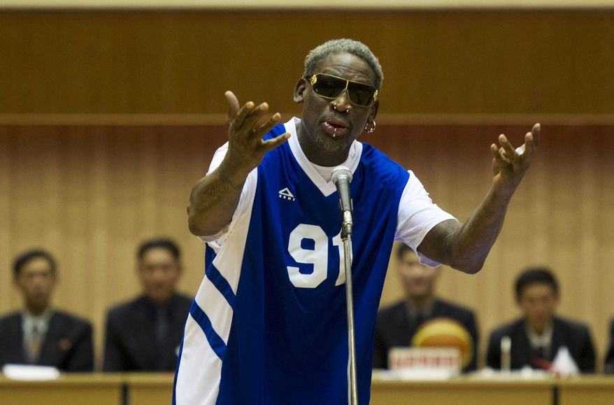 """Dennis Rodman sings """"Happy Birthday"""" to North Korean leader Kim Jong-un, seated above in the stands, before an exhibition basketball game at an indoor stadium in Pyongyang, North Korea on Wednesday, Jan. 8, 2014. (AP Photo/Kim Kwang Hyon, File)"""