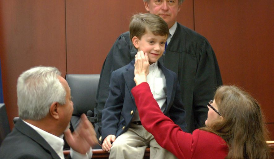 In this Monday, Dec. 1, 2014 photo, Lisa Colon, right, makes sure Brayden's face is clean before getting a picture with her husband, Felix Colon, left, and Judge George M. McFaddin Jr. at the Sumter County Judicial Center in Sumter, S.C. The judge takes pictures with the newly cemented families after the adoptions are finalized. (AP Photo/The Sumter Item, Jade Reynolds)