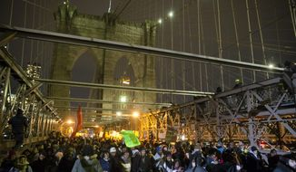Demonstrators march across the Brooklyn Bridge during a protest against a grand jury's decision not to indict the police officer involved in the death of Eric Garner, Thursday, Dec. 4, 2014, in New York. A grand jury cleared a white New York City police officer Wednesday in the videotaped chokehold death of Garner, an unarmed black man, who had been stopped on suspicion of selling loose, untaxed cigarettes. (AP Photo/John Minchillo)