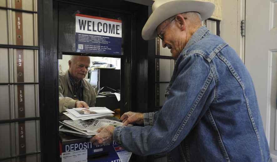 Jackie Skiles, 83, picks up his mail from postmaster Neal Wellman in Langtry, Texas, on Friday, Nov. 21, 2014. Skiles is one of the very residents still living in Langtry.  Once a bustling railroad and ranching hub an hour west of Del Rio, Langtry now is little more than a collection of empty homes and crumbling ruins, reduced to five families, a highway gas station and the state visitors center.   (AP Photo/The San Antonio Express-News, Billy Calzada)  RUMBO DE SAN ANTONIO OUT; NO SALES
