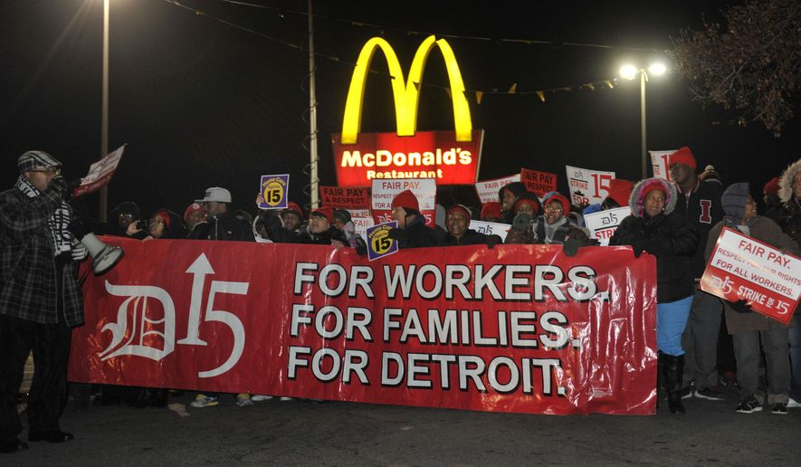 """People gather to protest for an increased minimum wage outside a McDonald's restaurant n Highland Park, Mich. The protests are part of a campaign called """"Fight for $15,"""" which has included several rounds of actions.  (AP Photo)"""