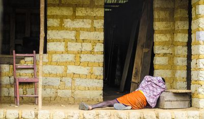 A man suffering from the Ebola virus lies on the floor outside a house in Port Loko Community, situated on the outskirts of Freetown, in Sierra Leone. (AP Photo/Michael Duff, File) ** FILE **