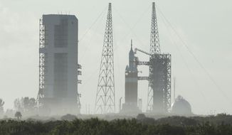A NASA Orion capsule on top of a Delta IV rocket sits on the pad at Complex 37 B at the Cape Canaveral Air Force Station, Thursday, Dec. 4, 2014, at Cape Canaveral, Fla. High wind gusts and a sticky valve forced NASA to scrubbed the early morning liftoff. (AP Photo/Chris O'Meara)