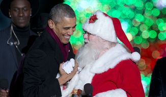 President Barack Obama greets Santa on stage during the National Christmas Tree lighting ceremony at the Ellipse near the White House in Washington, Thursday, Dec. 4, 2014. (AP Photo/Carolyn Kaster)