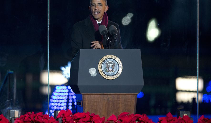President Barack Obama speaks from behind protective glass during the National Christmas Tree lighting ceremony at the Ellipse near the White House in Washington, Thursday, Dec. 4, 2014. (AP Photo/Carolyn Kaster)