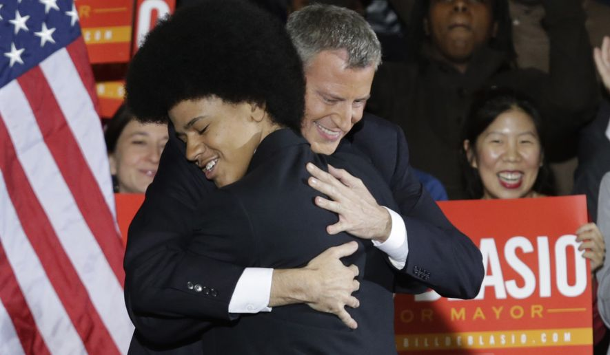 In this Nov. 5, 2013, file photo, Democratic Mayor-elect Bill de Blasio embraces his son Dante on stage after he was elected mayor of New York City in the Brooklyn borough of New York. As de Blasio spoke Wednesday, Dec. 3, 2014, in the aftermath of a grand jury's decision not to indict a white police officer in the chokehold death of Eric Garner, he drew upon the experiences of his own family to connect with disheartened New Yorkers. (AP Photo/Kathy Willens)