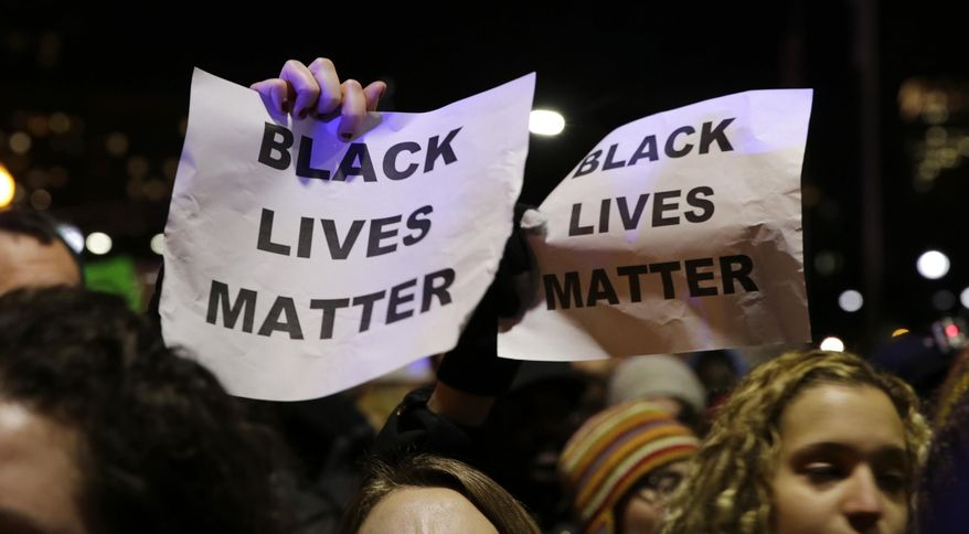 "In this Dec. 4, 2014 file photo, protestors in Boston hold up signs while chanting ""Black Lives Matter"" during a demonstration against the deaths of two unarmed black men at the hands of white police officers in New York City and Ferguson, Mo. (AP Photo/Charles Krupa, file) ** FILE **"