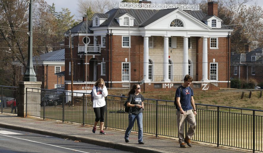 University of Virginia students walk to campus past the Phi Kappa Psi fraternity house at the University of Virginia in Charlottesville, Va. Rolling Stone is casting doubt on the account it published of a young woman who says she was gang-raped at a Phi Kappa Psi fraternity party at the school, saying there now appear to be discrepancies in the student's account. (AP Photo/Steve Helber, File) **FILE**