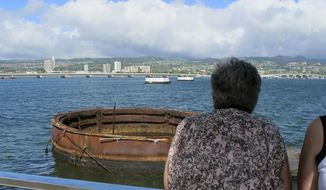 This Nov. 21, 2014 photo shows visitors looking out at the sunken USS Arizona from a memorial atop the rusting battleship in Pearl Harbor, Hawaii. The USS Arizona is one of the nation's most hallowed sites, an underwater grave for more than 900 sailors and Marines killed when Japan bombed Pearl Harbor and sank their ship in 1941, but it's now the scene of alleged rampant mismanagement. (AP Photo/Audrey McAvoy)
