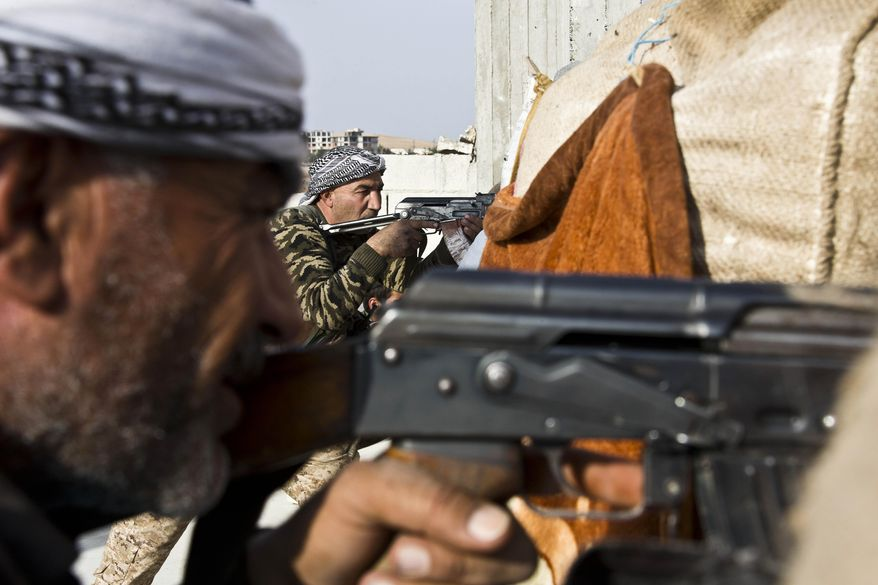 FIghters from the Free Syrian Army, left, and the Kurdish People's Protection Units (YPG), center, join forces to fight Islamic State group militants in Kobane, Syria, Nov. 19, 2014. (Associated Press) ** FILE **