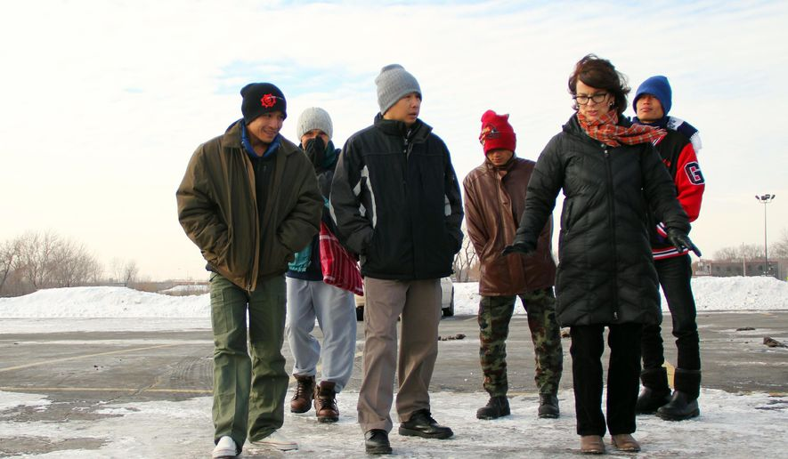 Elizabeth Ross, right, and Ghay Hu, center, give pointers to ethnic newcomers from a Thai refugee camp on how to tread across the ice in a St. Paul parking lot on Nov. 21, 2014.  Lessons on how to bundle up and use a thermostat are part of a cultural orientation offered by the International Institute of Minnesota, which helps resettle refugees.  (AP Photo/Minnesota Public Radio, Laura Yuen  )