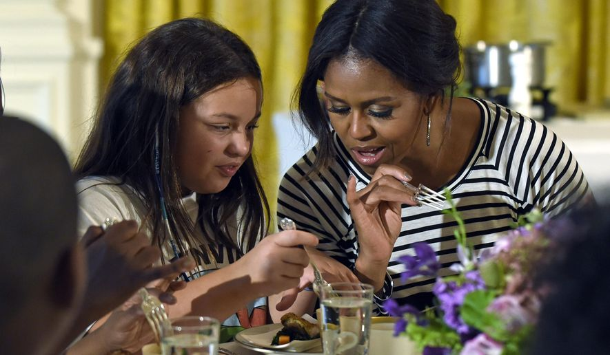 FILE - In this Oct. 14, 2014 file photo, first lady Michelle Obama and a student look over their plates as they eat lunch in the East Room of the White House in Washington following the annual fall harvest of the White House Kitchen Garden. House Republicans are making a final push this year to give schools a temporary break from healthier school meal standards. The school meal rules phased in since 2012. (AP Photo/Susan Walsh, File)