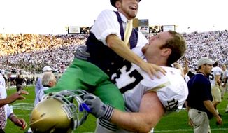 The Notre Dame mascot jumps into the arms of guard Ryan Gillis in East Lansing, Mich., Sept. 21, 2002. (Associated Press) ** FILE **