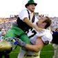 In this file photo, the Notre Dame mascot jumps into the arms of guard Ryan Gillis in East Lansing, Mich., Sept. 21, 2002. (Associated Press) ** FILE **