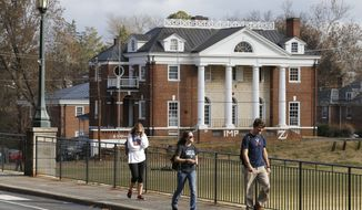 FILE - In this Monday, Nov. 24, 2014, file photo, University of Virginia students walk to campus past the Phi Kappa Psi fraternity house at the University of Virginia in Charlottesville, Va. Rolling Stone is casting doubt on the account it published of a young woman who says she was gang-raped at a Phi Kappa Psi fraternity party at the school, saying there now appear to be discrepancies in the student's account. (AP Photo/Steve Helber, File) **FILE**