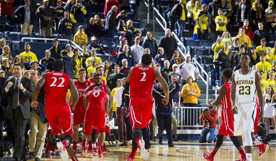 N.J.I.T. head coach Jim Engles, far left, celebrates with his players as Michigan guard Caris LeVert (23) walks off the court after an NCAA college basketball game at Crisler Center in Ann Arbor, Mich., Saturday, Dec. 6, 2014. N.J.I.T. won 72-70. (AP Photo/Tony Ding)