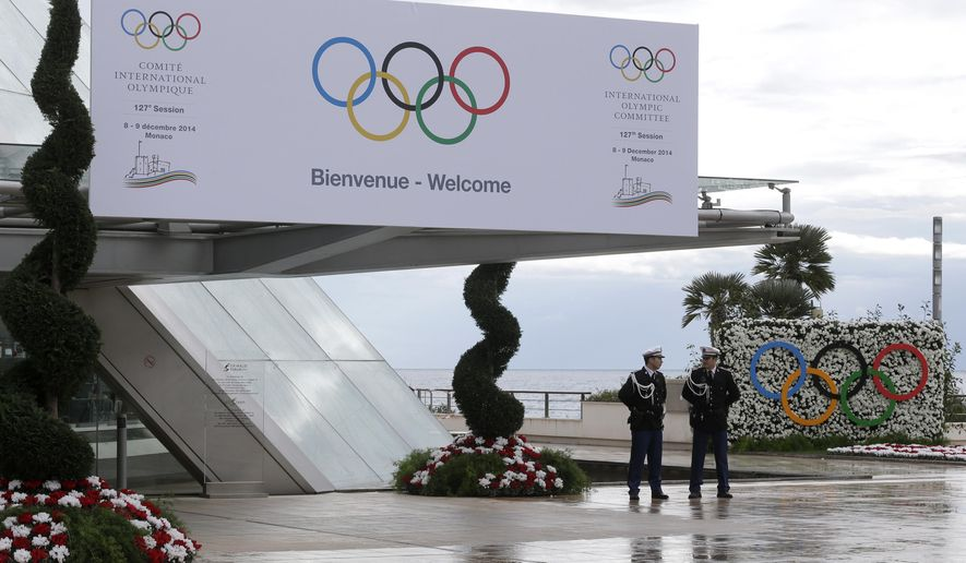 Monaco policemen stand in front of the entrance of the International Olympic Committee executive board meeting in Monaco, Friday, Dec. 5, 2014.  The 127th IOC session will be opening on Sunday Dec. 7. (AP Photo/Lionel Cironneau)
