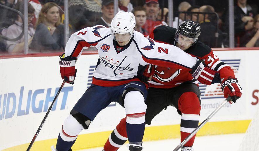 Washington Capitals defenseman Matt Niskanen, left, skates against New Jersey Devils right wing Mike Sislo during the second period of an NHL hockey game, Saturday, Dec. 6, 2014, in Newark, N.J. (AP Photo/Julio Cortez)