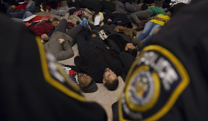 """Protesters participate in a """"die-in"""" at Grand Central Station as police stand guard during a demonstration against a grand jury's decision not to indict the police officer involved in the death of Eric Garner, Saturday, Dec. 6, 2014, in New York. (AP Photo/John Minchillo)"""