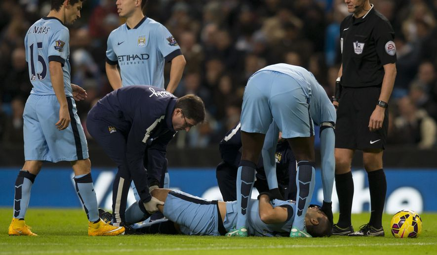 Manchester City's Sergio Aguero is treated on the pitch before being taken off injured during the English Premier League soccer match between Manchester City and Everton at the Etihad Stadium, Manchester, England, Saturday Dec. 6, 2014. (AP Photo/Jon Super)