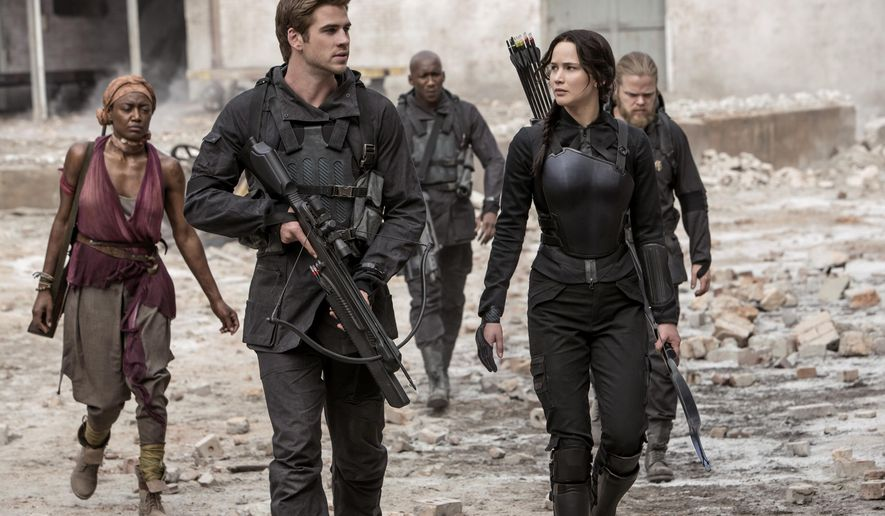 """In this image released by Lionsgate, Jennifer Lawrence portrays Katniss Everdeen, right, and Liam Hemsworth portrays Gale Hawthorne in a scene from """"The Hunger Games: Mockingjay Part 1."""" (AP Photo/Lionsgate, Murray Close)"""