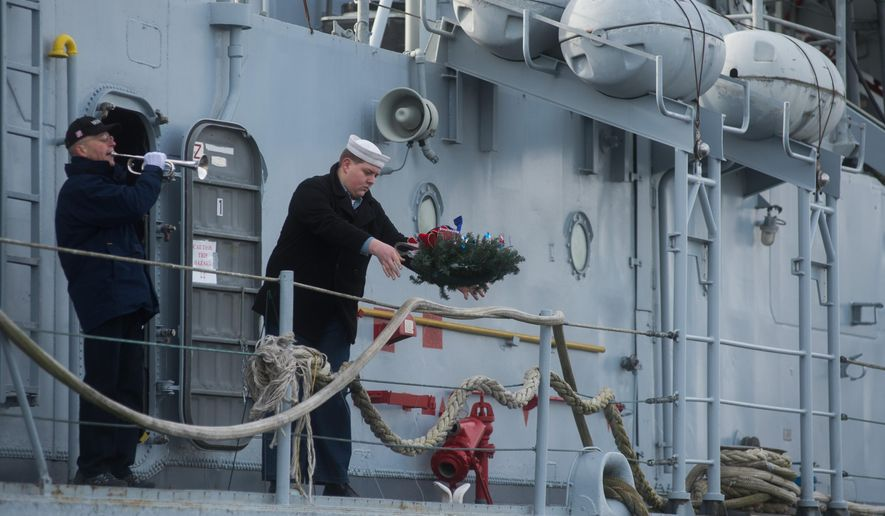 A wreath is thrown from aboard the USS Edson during a Pearl Harbor memorial ceremony Sunday, Dec. 7, at the USS Edson in Bangor Township, Mich.  (AP Photo/The Bay City Times, Yfat Yossifor) LOCAL TELEVISION OUT; LOCAL INTERNET OUT