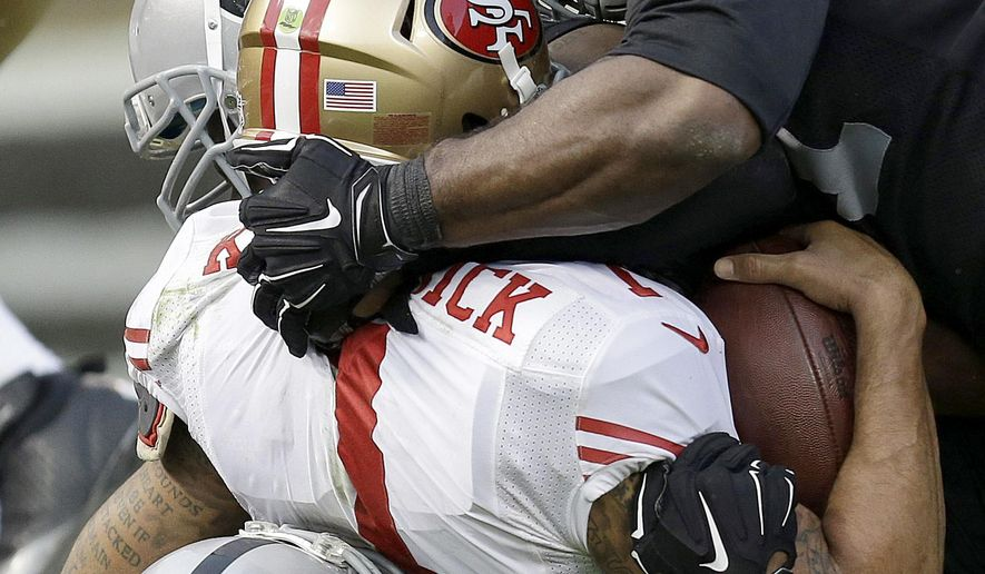 San Francisco 49ers quarterback Colin Kaepernick, center, is sacked by Oakland Raiders outside linebacker Khalil Mack, bottom, as defensive end Justin Tuck (91) converges during the fourth quarter of an NFL football game in Oakland, Calif., Sunday, Dec. 7, 2014. The Raiders won 24-13. (AP Photo/Ben Margot)
