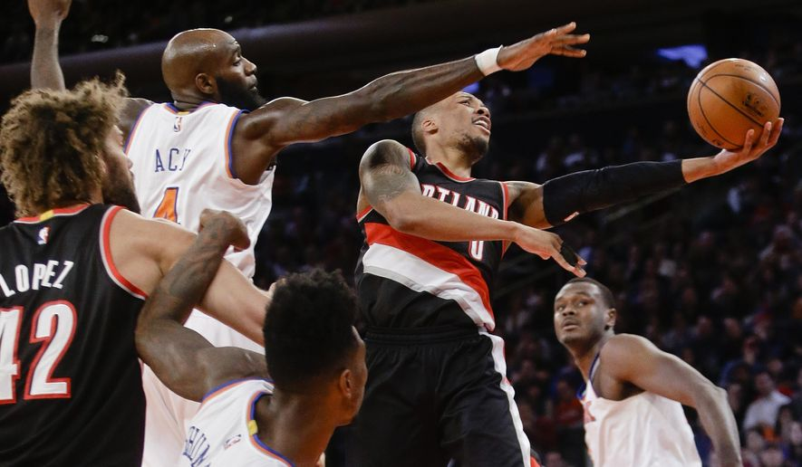 Portland Trail Blazers' Damian Lillard (0) drives past New York Knicks' Quincy Acy (4) during the first half of an NBA basketball game Sunday, Dec. 7, 2014, in New York.  (AP Photo/Frank Franklin II)