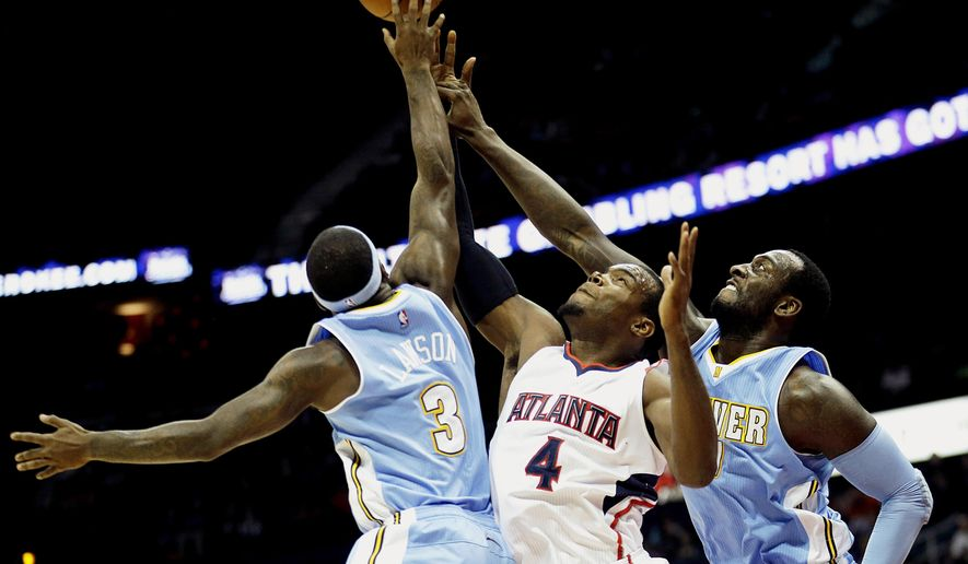 Atlanta Hawks' Paul Millsap (4) reaches for a rebound against Denver Nuggets' Ty Lawson, left, and J.J. Hickson in the first quarter of an NBA basketball game, Sunday, Dec. 7, 2014, in Atlanta. (AP Photo/David Goldman)