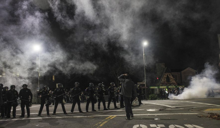 Demonstrators toss out smoke bombs during a march in Berkeley, California on Saturday, Dec. 6, 2014. Two officers were injured Saturday night as a California protest over police killings turned violent with protesters smashing windows and throwing rocks and bricks at police, who responded by firing tear gas, authorities said. Demonstrators were responding to the grand jury verdicts in the shooting death of Michael Brown in Ferguson, Missouri and the chokehold death of Eric Garner in New York City by local police officers in their communities. (AP Photo/San Francisco Chronicle, Sam Wolson)