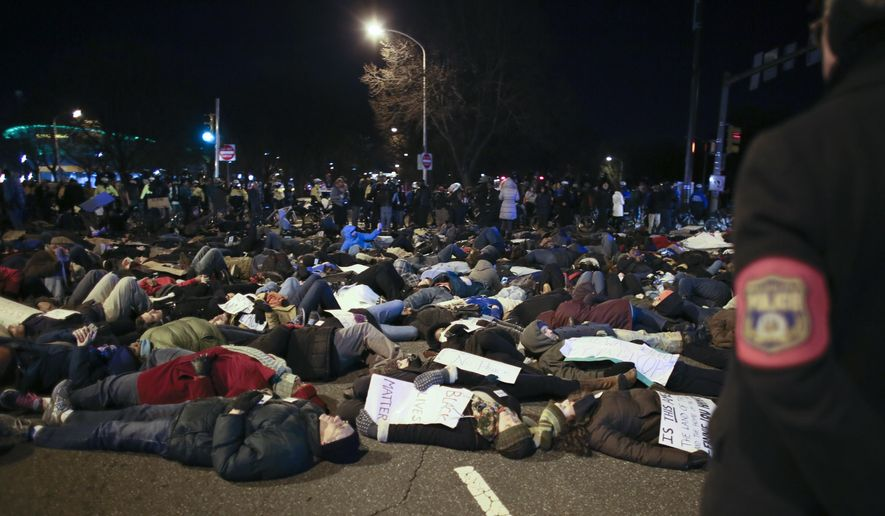 People participate in a die-in demonstration, Sunday Dec. 7, 2014, in Philadelphia, protesting the deaths of two unarmed black men at the hands of police.  Demonstrators blocked traffic and conducted a die-in on the streets surrounding the sports stadium complex in South Philadelphia following an NFL game. (AP Photo/ Joseph Kaczmarek)