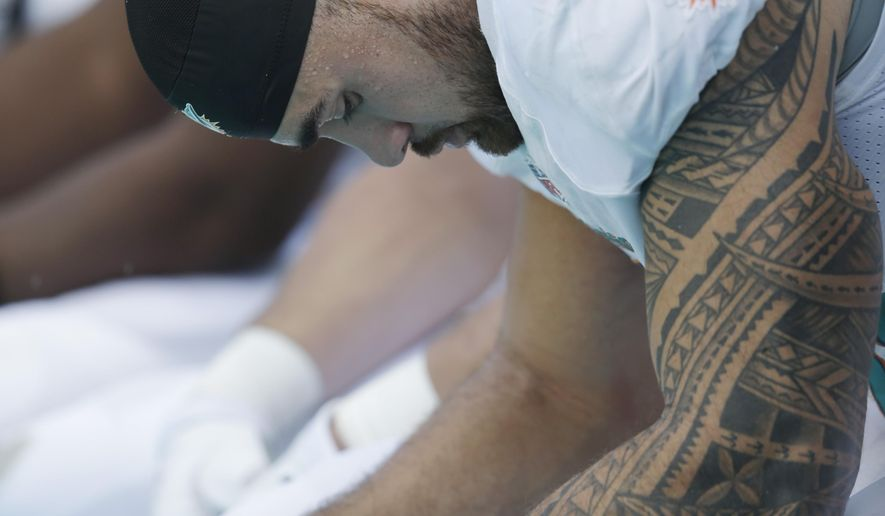Miami Dolphins outside linebacker Koa Misi sits on the bench during the final minutes of the second half of an NFL football game against the Baltimore Ravens, Sunday, Dec. 7, 2014, in Miami Gardens, Fla. The Ravens defeated the Dolphins 28-13. (AP Photo/Wilfredo Lee)