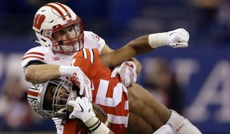 Ohio State running back Ezekiel Elliott, front, is brought down by Wisconsin safety Michael Caputo after running for yardage during the first half of the Big Ten Conference championship NCAA college football game Saturday, Dec. 6, 2014, in Indianapolis. (AP Photo/Michael Conroy)
